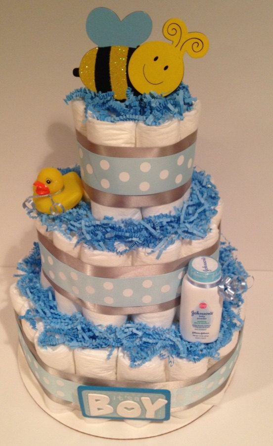 A diaper cake will make a beautiful lasting impression at any baby shower! Perfect centerpiece or welcome baby gift for expecting parents!  Diaper Cake includes:  - (40) Size 1 Diapers (Bottom and Top Tier) - (17) Size 2 Diapers (Middle Tier) - (1) Bumble Bee Die Cut - (1) Its a Boy Die Cut - (1) Rubber Ducky Bath Toy - (1) Johnsons Baby Powder Bottle  Made with:  - 12 White Cake Board - Decorative ribbons, and blue crinkle paper.  ** Measures about 14 tall **  All Diapers Cakes are placed…