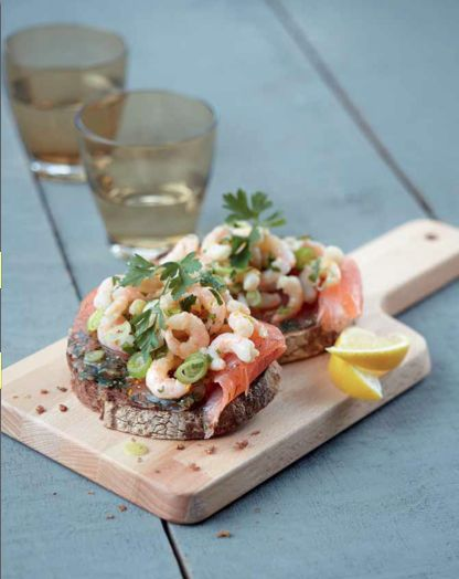 Crostini di salmone con gamberetti - Scongela salmone e gamberetti. Grattugia la buccia di un limone e spremilo. Trita il prezzemolo e metti da parte dei rametti. Taglia finemente le cipolline. Unisci i gamberetti, la buccia di limone grattugiata, il prezzemolo, la cipollina e un goccio d'olio d'oliva. Insaporisci con sale, pepe e succo di limone. Tosta le fette di pane. Disponile nei piatti e adagia sopra le fettine di salmone. Versa sopra una cucchiaiata di gamberetti al limone.