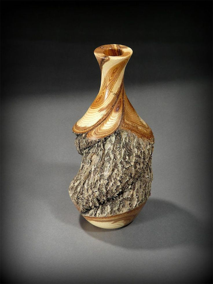 Ray Asselin creates artistic vases out of logs, featuring both polished surfaces and the untouched grain of the wood.