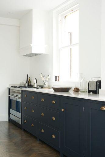 armoires de cuisine bleu minéral avec poignées en laiton et parquet foncé