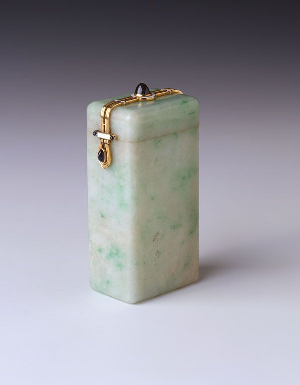 Box, mottled green and white jade box with gold strap and white enamel mounted lid fastner inset with cabochon sapphires. Cartier. c.1910
