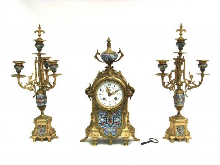 """Salle des ventes ABC : Garniture de cheminée, bronzes dorés et émaux cloisonnés, les candélabres à trois bras de lumières plus emplacement pour l'étouffoir, la pendule à cadran émaillè à chiffres Arabes, le mécanisme numérotè, marquè L.F. et portant une marque ronde de """"Japy Frères et Compagnie, Grande Médaille d'Honneur"""". Hauteur : 37 et 42 cm, l'ensemble de style Louis XVI époque Napoléon III"""