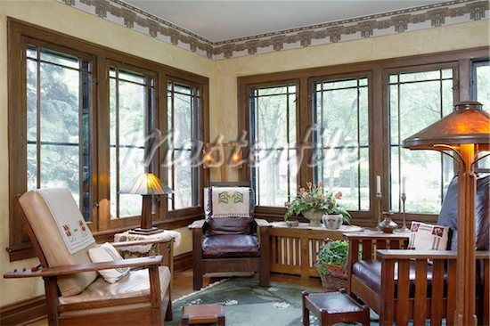 SUNROOM: Wide mullion windows, yellow walls, stylized Craftsman wallpaper border, mica shade on floor lamp, Arts and Crafts style leather upholstered oak furniture, embroidered linens Stock Photos