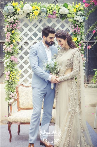 candid shot, couple holding hands shot, champagne color sari, sequins sari, pastel blue tuxedo, floral backdrop