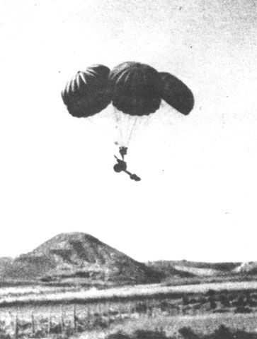 Antitank gun, attached to five parachutes, is dropped over Crete.