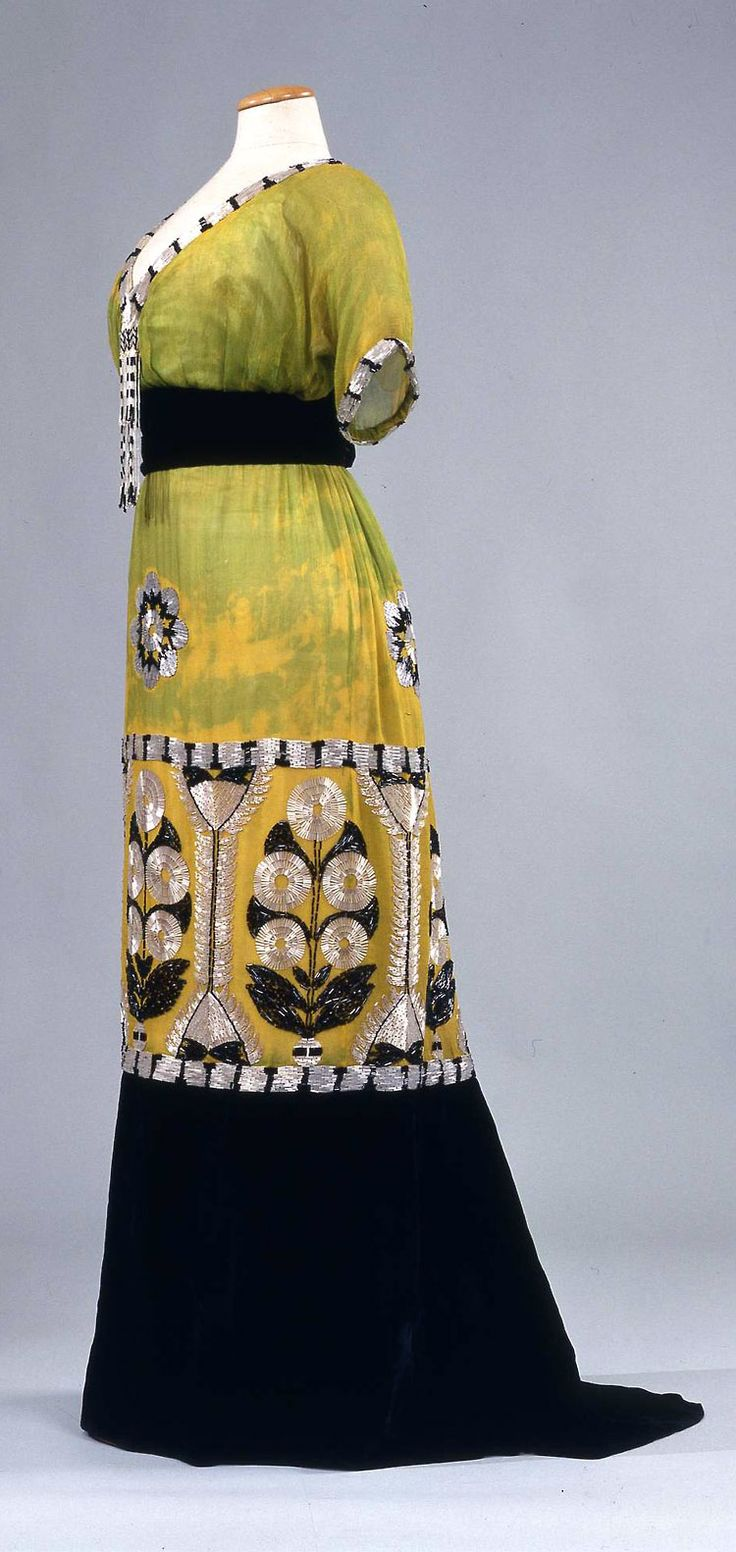 Evening dress, Sartoria A La Ville de Lyon Raphael Goudstikker, Naples, ca. 1913. Green & yellow chiffon with belt and deep flounce of black velvet, embroidered with glass beads & straws in stylized flower motifs.