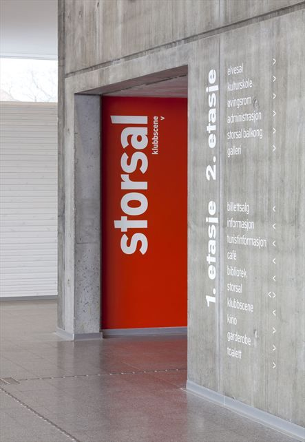 The Arch Cultural Centre - The solid color on the entry wall, surrounded by the endless grey marble, creates a simple but extremely noticeable ID marker. The wayfinding list on the side, done in white directly on the marble instead of having a separate substrate material, allows the orange ID marker to keep it's dominate attraction for the viewer.