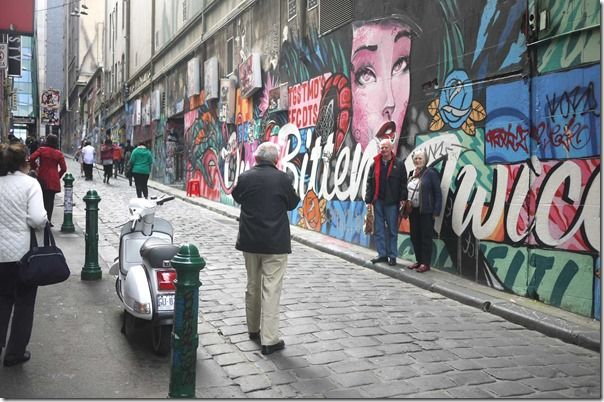 Tourists taking photos with street art at Hosier Lane (off Flinders street), Melbourne, Australia.