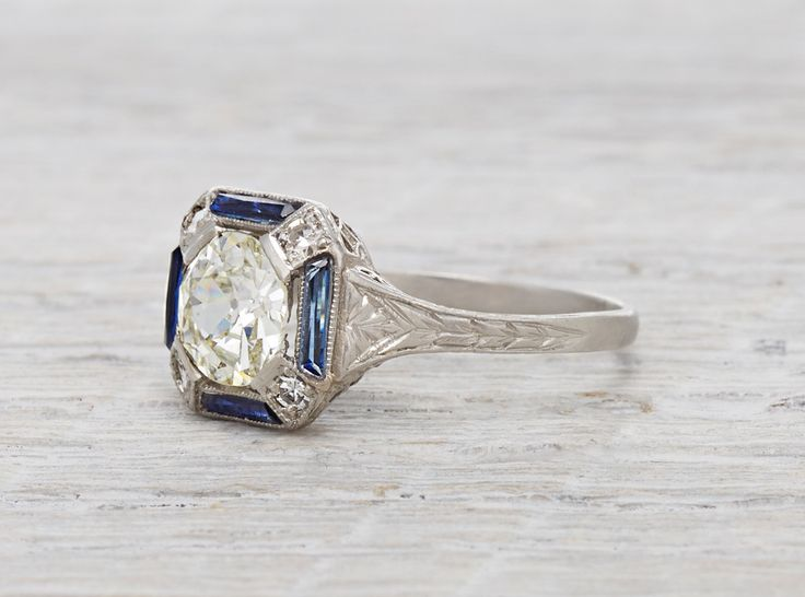 Art Deco vintage engagement ring made in platinum and centered with an approximatey 1.17 carat EGL certified old European cut diamond with I-J color and SI1 clarity. Accented with four calibre cut sap