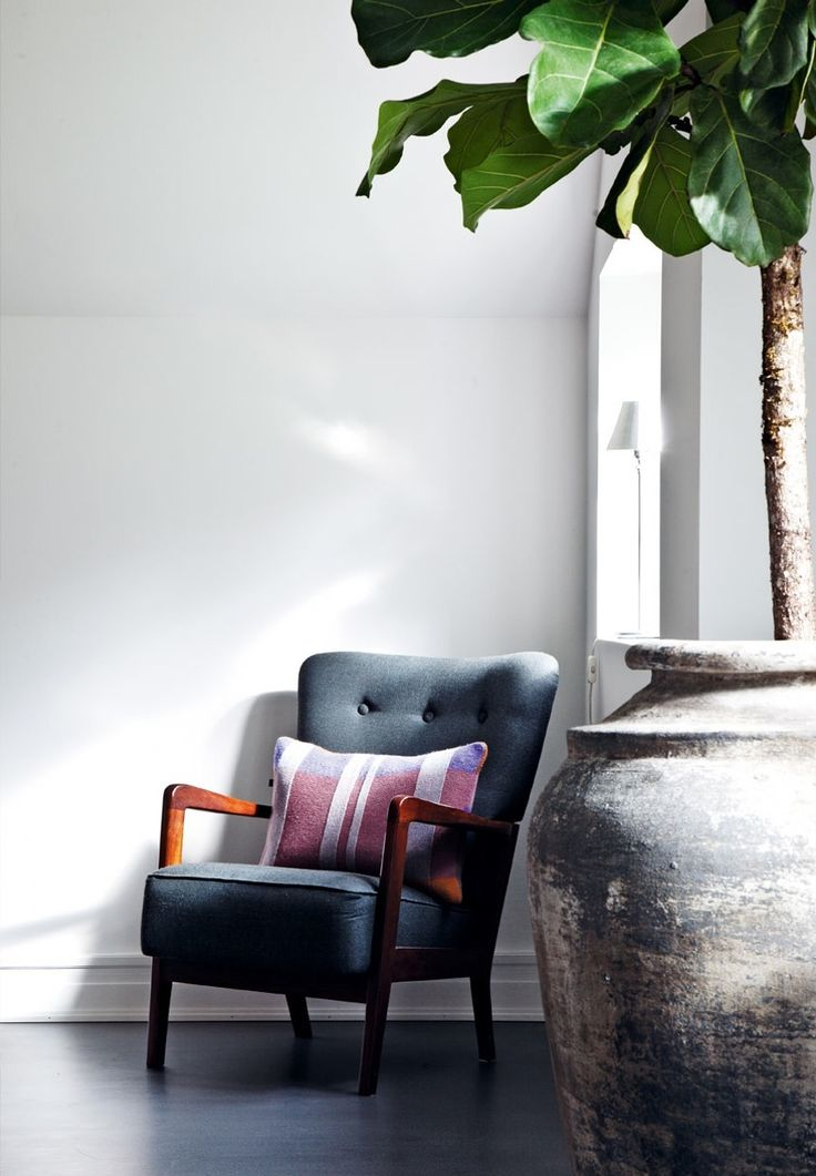 Reading corner with a big fiddle leaf fig and the Finnegan Chair, which is designed and produced by Eleanor Home. Pillow from Caravane.