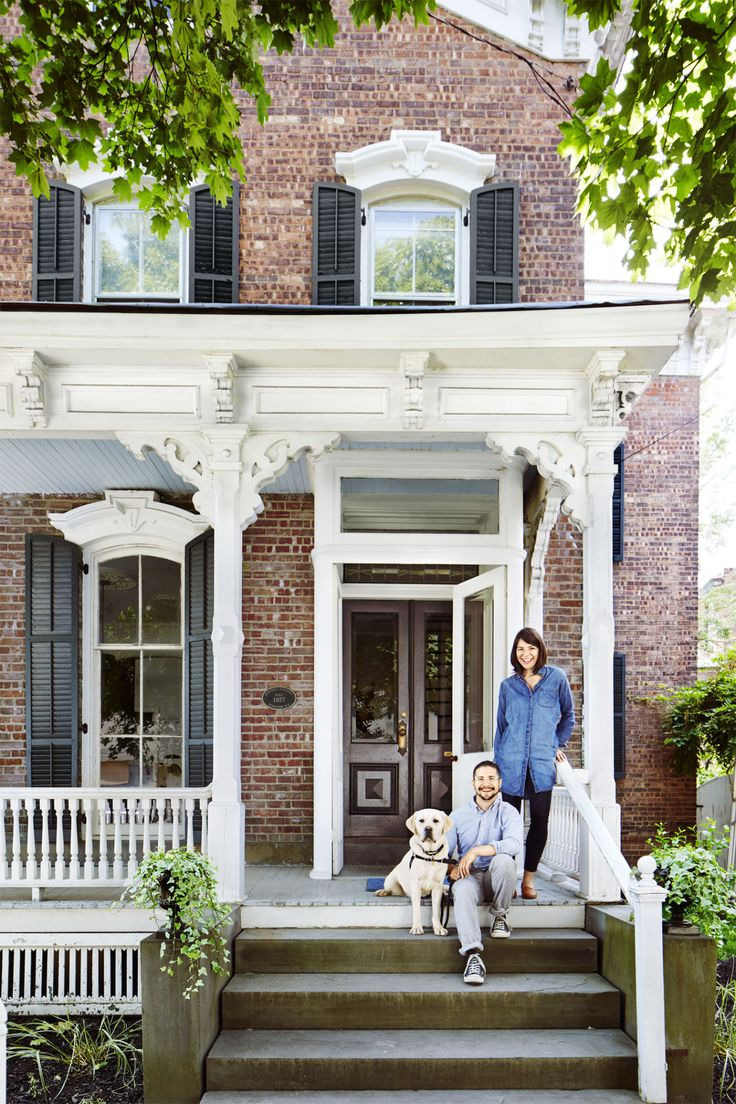 Beautiful classic brick exterior with black shutters and white Victorian porch details