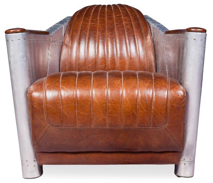 Reposez-vous aux creux des coussins rembourrés recouvert de cuir premium marron d'excellente qualité. Sa structure en bois est très solide et stable, elle soutient une assise moelleuse qui vous garantit confort et détente. Les accoudoirs de ce fauteuil atypique sont acier inoxydable ce qui lui donne un côté futuriste et moderne.   General H 73 x L 75 x P 91 cm Siège  L 62 x P 59 cm  Dossier H 45 cm Poids36Kg Revêtement : Cuir premium Remplissage : Mousse Structure : Bois Pieds : Aluminium