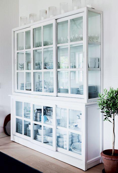 Et stilrent Bulderby hus - Der er ingen overskabe i køkkenet, så familien har et stort smukt vitrineskab til at opbevare al service i. Øverst på skabet står enkle glaslanterner, til når der skal hygges. Skabet er fra Ilva.