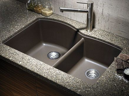 Composite stone sink. No more water spots! Also I like when the center divider is lower than average. Easier to switch from one side to the other and not move the faucet, and makes it easier to fill or wash larger items