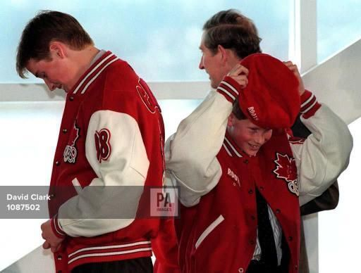 march 25,1998--Prince William (L) buttons his Canadian Olympic team jacket while his brother Harry puts on a hat and their father Prince Charles looks out a window in Vancouver. The trio is on a ski vacation and are making their first public appearance since the death of Princess Diana