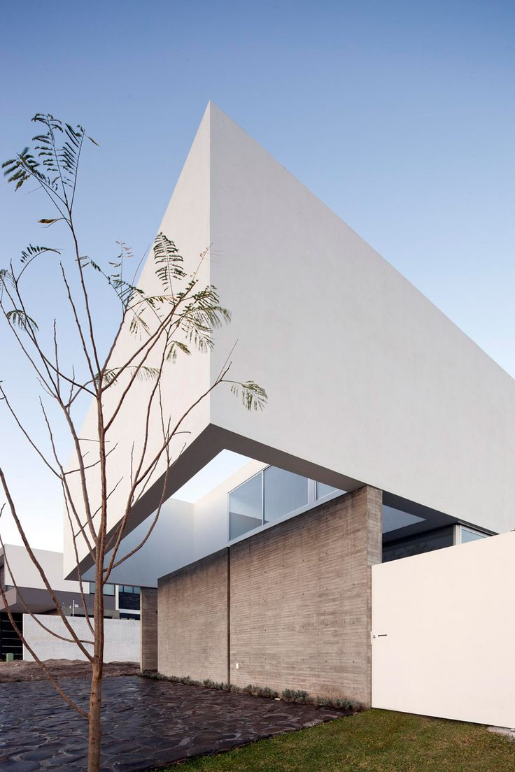 A white-rendered concrete screen extends from the upper floor of this house near Guadalajara, Mexico, blocking views to the street but framing a perspective of the garden and sky
