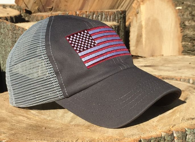 Embroidered American flag design in red on a charcoal and gray mesh backed hat with a snap back adjustment on the back. No button on the top, so you can wear this with ear protection and headphones. T