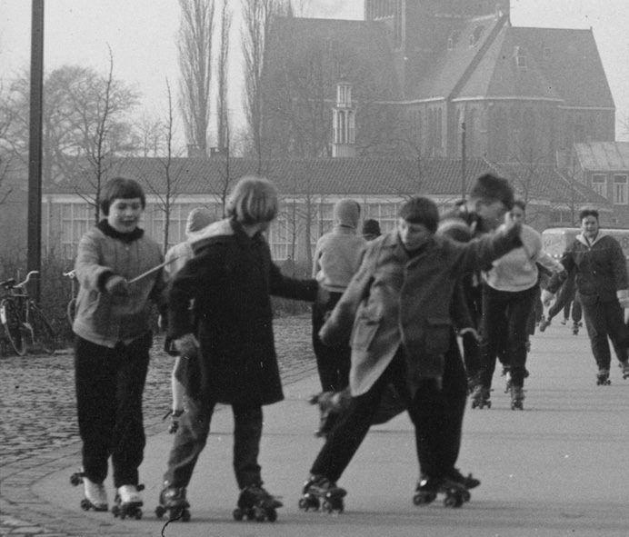 Rolschaatsende jeugd op de rolschaatsbaan op het Schoolakkerplein in 1954, met op de achtergrond de zojuist opgeleverde school aan de Viandenlaan.