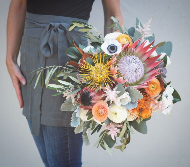 Colorful protea bouquet with anemones, ranunculus, astilbe olive, magnolia, dusty miller and pincushions.  Love this bouquet!  STEMS Floral Design + Productions | Austin Florist | Floral Design | Weddings + Events | Central Texas