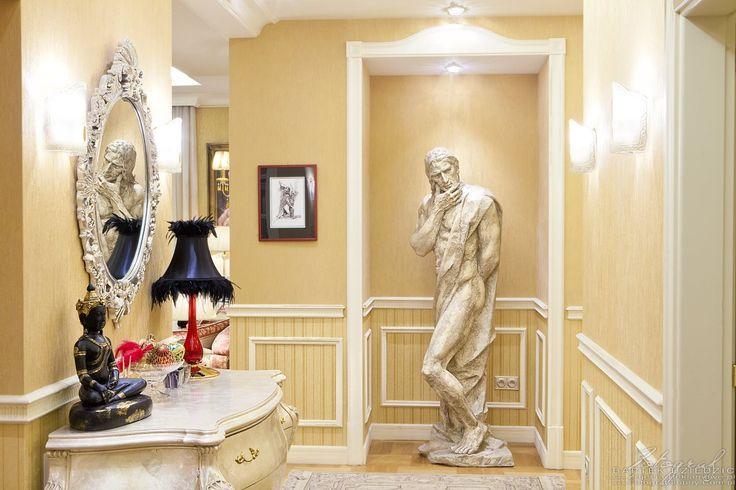 Projektowanie wnęrz Kraków. Hol widok od wejścia po lewej piękna komoda na wprost rzeźba, statua mężczyzny.