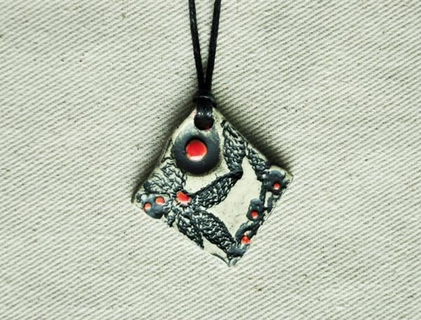 Black & White With Red Accent-Matte Finish Pendant  This pendant is handmade from stoneware clay that was imprinted with a vintage lace pattern. After a first kiln firing, it was washed with a stain and spot glazed with red.  Aradia Gallery
