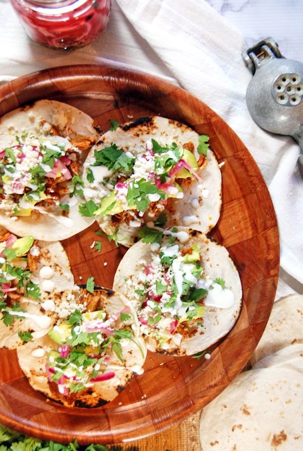 Shredded chicken tacos get kicked up a notch with ancho achiote paste, pickled red onions, avocado, and crema.
