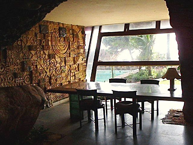 Moon Dust Residence, Madh Island: View of the dining area with a mural wall at left; beyond the glazed slanted wall is the beach   Archnet