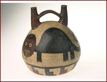 Kruik met tweemaal de schildering van een kat of poema met uitstekende tong. Hij heeft een rond hoofd met ronde ogen. Deze manier van afbeelden is direct afgeleid van de Oculate Being van de voorafgaande Paracas-cultuur. Onderlangs loopt een band met trapmotieven.