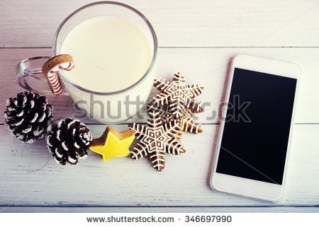 Concept photo Stay in touch at holidays Christmas cookies with cup of milk pine cones and mobile phone at a red background Top view
