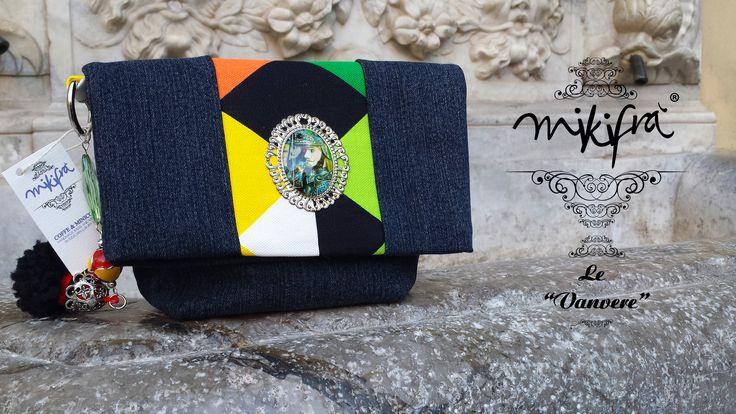 Pochette Rinalda: Mini Bag in jeans e cotone colorato a fantasia triangolare. Decorazione centrale con filigrana e resina raffigurante pupo siciliano. Manichetto gioiello con ceramiche colorate, resine e pon pon siciliano.