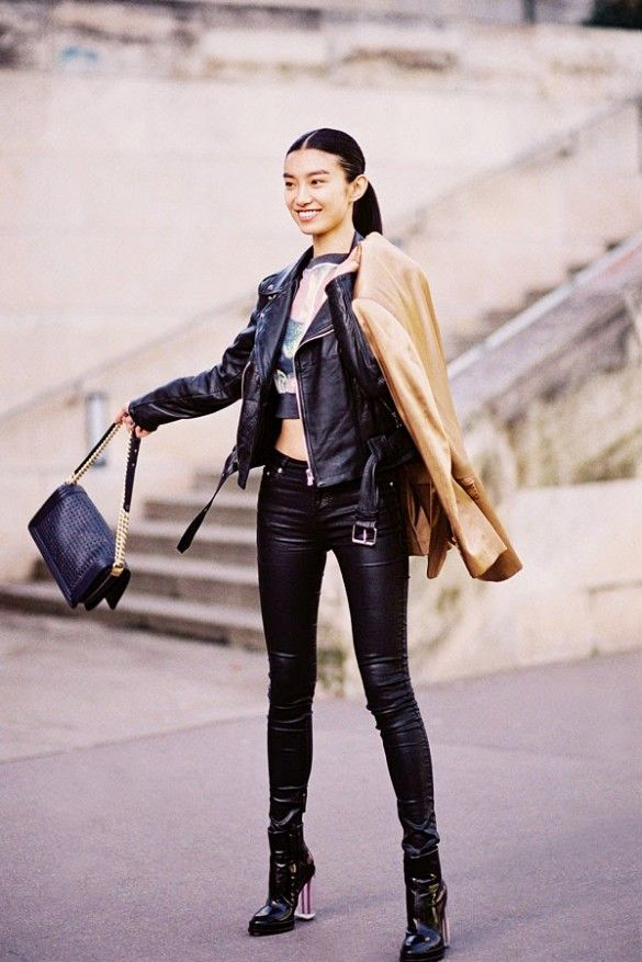 A graphic crop top is worn with leather jacket, leather pants, patent leather boots and a camel jacket.
