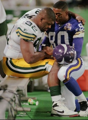 This is such an inspiring picture.  Cris Carter praying on the sidelines with Reggie White.