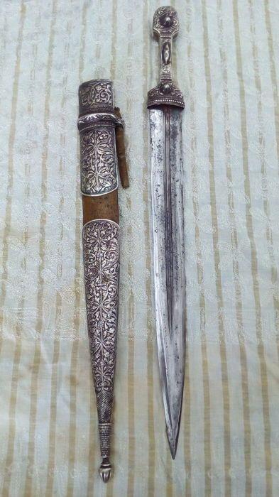 """dolk Kaukasische """"Kingjal""""  """"Kindjal"""" uit de Kaukasus met gevest en schede bedekt met nielloed zilverDecoraties gebeiteld met loof van palmbladeren en roosjes.Op de achterkant van de schede een inscriptie in de Armeense tekens (de naam van de eigenaar)Mes met fullers met gestileerde florale decoratie gegraveerd met etsen.Zuidelijke Kaukasus61 cm.Gewicht van de schede 414 gGewicht van het blad 632 gVerzending via colissimo  EUR 600.00  Meer informatie"""