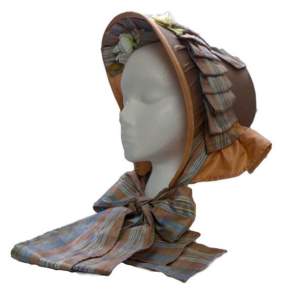 "1853-63 ___ Bonnet (reproduction) ___ Taupe silk taffeta exterior, peach silk taffeta lining and bavolet. Frame constructed of buckram and wire. Trimmed with silk shantung plaid ribbons and artificial flowers. ___ Bonnet shown on a 21"" foam head and is recommended for head sizes 21 – 22"". ___ Bonnet Dimension: Height 11"", Width 9"", Depth 8"" (top of the brim to tip), Ties 39"" long ___ Excellent for a middle class impression. ___ photo 1"