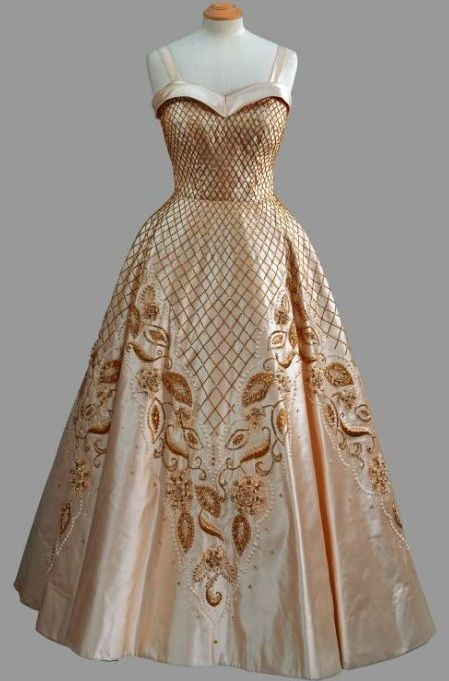 "Evening Gown, Norman Hartnell: 1957, silk with with lattice and foliate beaded embroidery. ""Worn [by HRH Queen Elizabeth II] for official portraits of The Queen taken by Baron in 1957."""