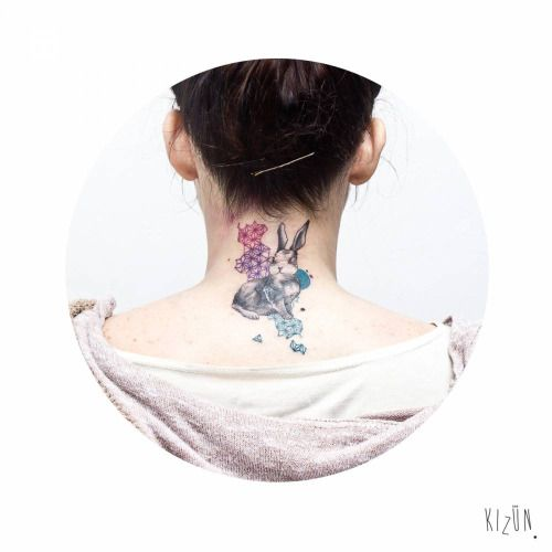 Graphic style rabbit tattoo on the back of the neck. Tattoo...