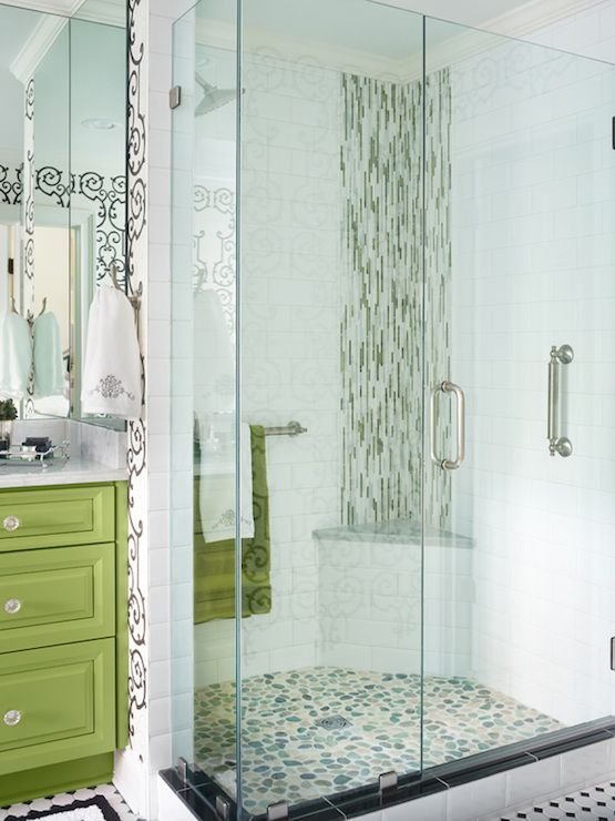 Contemporary bathroom features walls clad in black and white scroll wallpaper framing an apple green vanity topped with white marble and paired with wraparound frameless mirrors over black and white border bath mats atop black and white harlequin tiled floor.