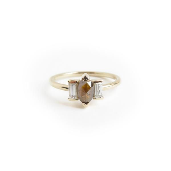 RUMI   The Unfolding   A one of a kind 9ct yellow gold ring with a centered 0.411ct marquise shaped brown diamond, flanked by two 15ct baguette white diamonds.