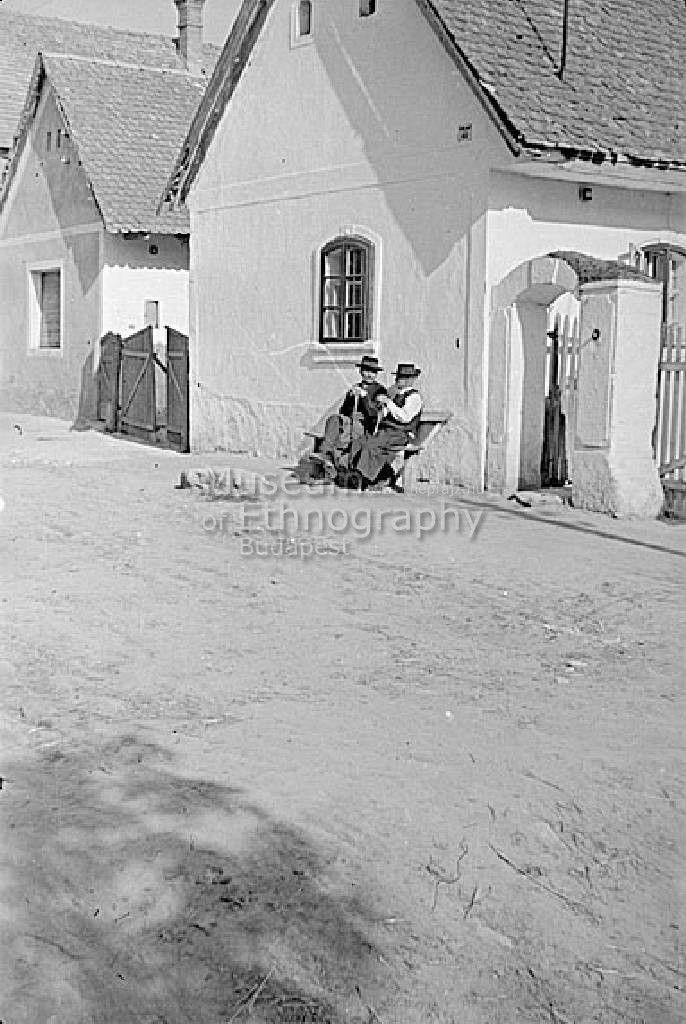 A felvétel vasárnap délelőtt készült: beszélgető öregek a padon - Páty, 1952. Fotó: Hofer Tamás - Néprajzi Múzeum | Online Gyűjtemények - Etnológiai Archívum, Fényképgyűjtemény