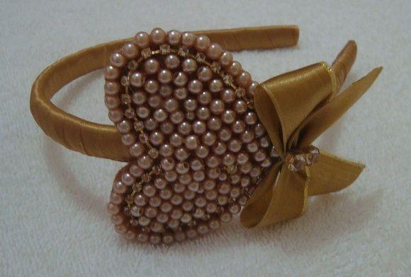 Tiara revestida em fita cetim dourada co lindo coração bordado em pérolas, strass e laço dourado. R$ 24,90
