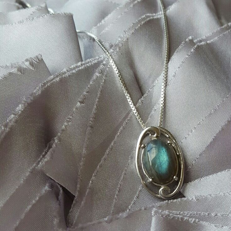 Sterling Silver Swirl Pendant with Magnificent Labradorite Oval has a sense of mystery; of connecting us to the unknown and of balance and insight.. Labradorite appears greyish brown until light hits it and reveals an intruiging blue