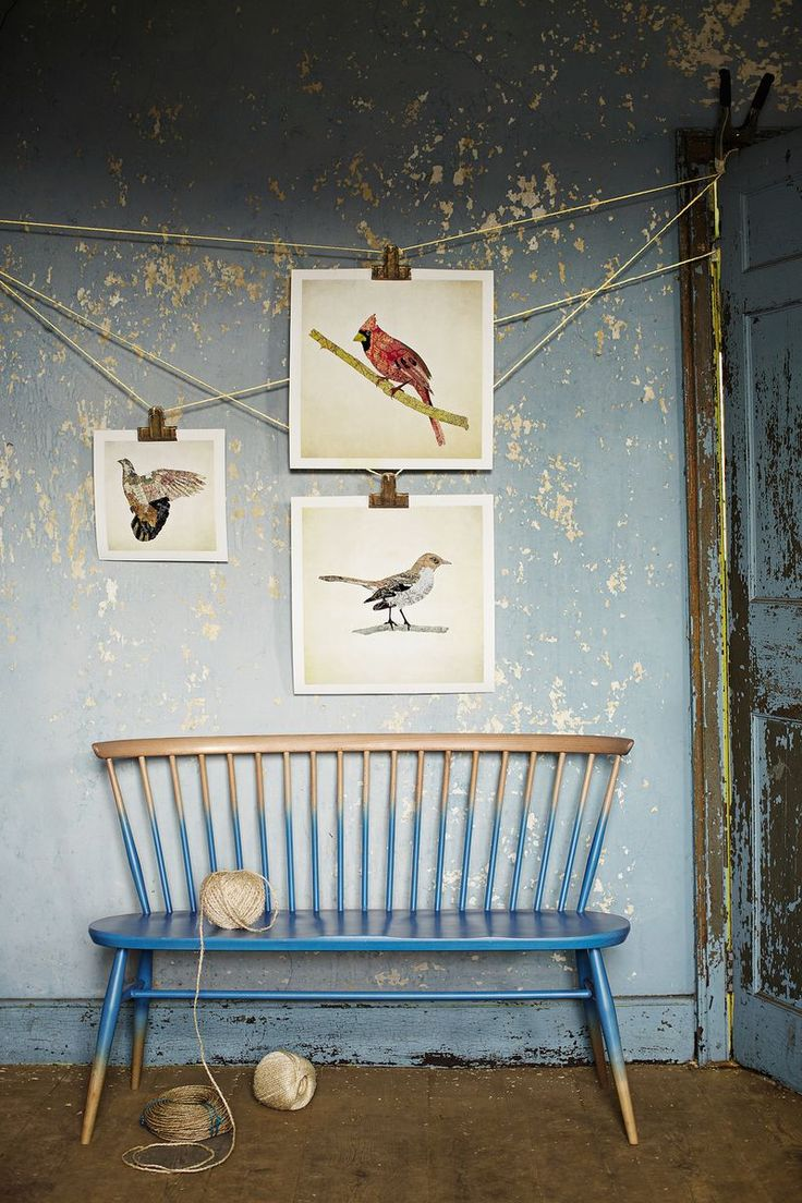 You can create drama on a wall by hanging pieces of art asymetrically. Here, some string and some art clips are used to fashion a hanging apparatus that makes a few simple prints look like an art installation.