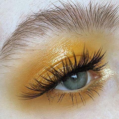 Yellow eye make up. Natural messy brows.