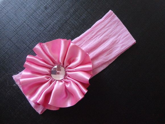 Faixa em meia de seda rosa com flor em fita de cetim rosa.