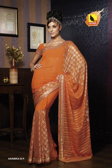 orange saree with gold border, some red.  (this one has a bit too much on the pallu for my taste)