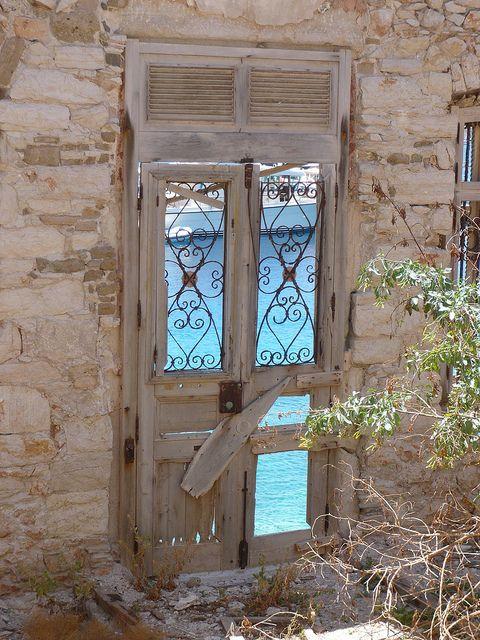 Timeworn doors to the sea in Greece.