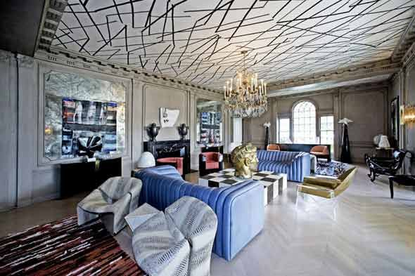 In the paneled and pilastered den, there's a cacophonous but clear-headed mélange of 1970s decor: large-scale herring bone hardwood floors, a ceiling painted to look like a game of Pick-up Sticks, a glitzy antique crystal chandelier, and a black and white checked slab coffee table on top of which sits a shockingly large bronze bust. It's all wrong for a thousand reasons and yet, somehow, Wearstler makes it work.  Kelly Wearstler