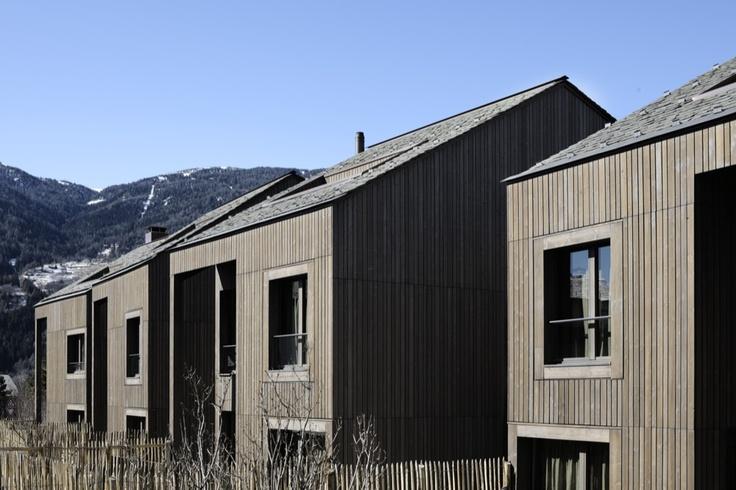 Una sequenza di quattro edifici alti e stretti, vestiti sobriamente di legno di larice.