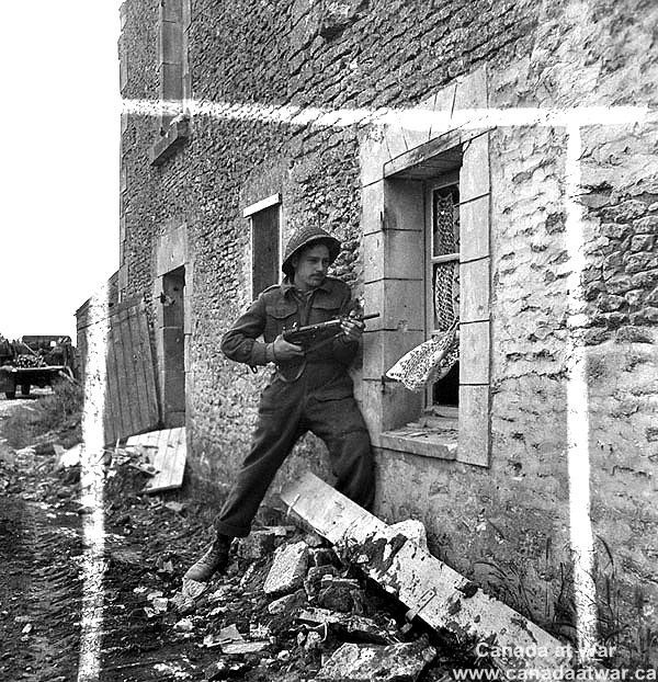 Canadians capture Caen - A Royal Canadian Engineer (R.C.E.) Sapper armed with a Sten Gun, searching buildings for enemy snipers. July 9, 1944, Gruchy, France.