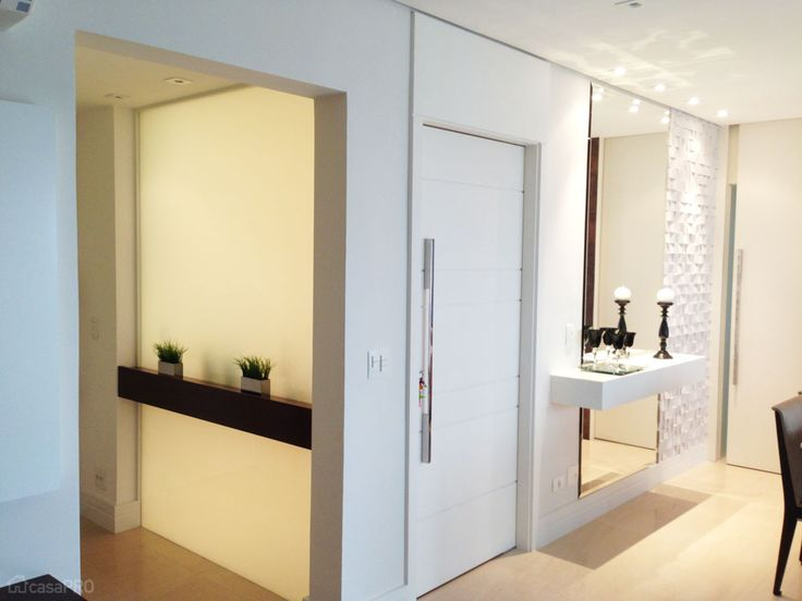 Hall de entrada de apartamento residencial. Separado por parede de vidro serigrafado fixo, com aparador de madeira que serve a ambos os lados. Piso de limestone Mont Dore. Projeto de AT arquitetura.